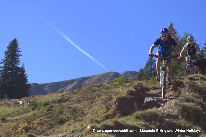 Two mountain bikers on Alps singletrack