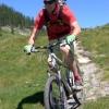 Rider in red descending on alpine singletrack